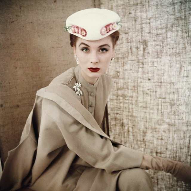 ca. March 1953 --- Model wearing beige button-front suit with white flowered hat, both from Christian Dior. --- Image by © Condé Nast Archive/Corbis